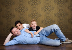 Happy family. Beautiful family portrait lying on the floor. Mother, father and son are happy and smiling Stock Photos