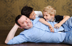 Happy family. Beautiful family portrait lying on the floor. Mother, father and son are happy and smiling Stock Photography