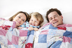 Happy Family in bed. A smiling family under the a blanket in bed Royalty Free Stock Image