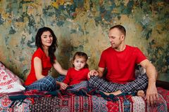 Happy Family on the bed. Mom, dad and daughter in red T-shirts and pajamas are playing. Royalty Free Stock Photo