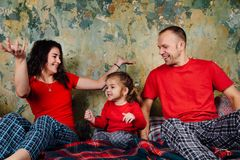 Happy Family on the bed. Mom, dad and daughter in red T-shirts and pajamas are playing. Royalty Free Stock Image