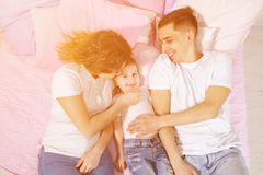 Happy family in bed, mom, son and dad are kissing and hugging together. Portrait of happy young family in bed, mom, son and dad are kissing and hugging together stock images