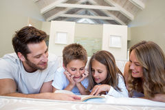 Happy family on the bed reading book Royalty Free Stock Images