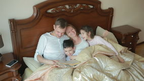 Happy family on bed reading a book out loud at home stock video footage