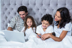 Happy family in bed shopping online Stock Photography