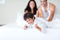 Happy family on bed with thumbs up Royalty Free Stock Image