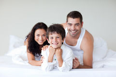 Happy family on bed with thumbs up Royalty Free Stock Images