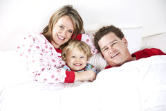 Happy Family at bedtime. A smiling family under the a blanket in bed Stock Photos