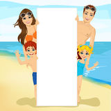 Happy family behind a white blank billboard at the beach Royalty Free Stock Photos