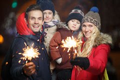 Happy family with bengal lights. In park at night in new year Stock Photos