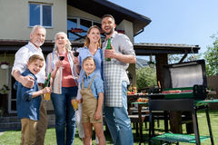 Happy family with beverages looking aside while having barbecue together Stock Image