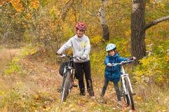 Happy family on bikes cycling outdoors stock photo