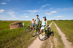 Happy family on bikes standing in a field Stock Image