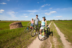 Happy family on bikes standing in a field Royalty Free Stock Photography