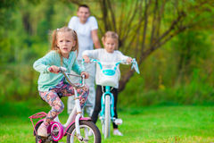 Happy family biking outdoors at the park Stock Photo