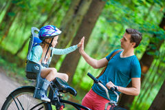 Happy family biking outdoors at the park. Happy family biking at summer warm day Stock Images