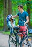 Happy family biking outdoors at the park Stock Photos