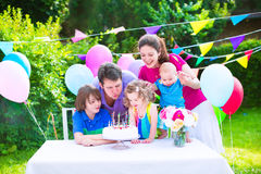Happy family at birthday party. Happy big family with three kids - school age boy, toddler girl and a little baby enjoying birthday party with a cake blowing royalty free stock photos