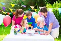 Happy family at a birthday party. Happy big family - young parents, grandmother, three kids, teenage boy, toddler girl and little baby celebrating birthday party royalty free stock photo