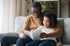 Happy family black father and kid daughter reading story book royalty free stock image