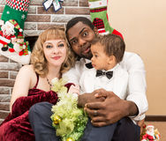 Happy family: black father, mom and baby boy by fireplace. Christmas Royalty Free Stock Photography