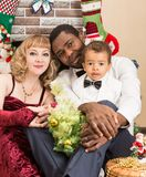 Happy family: black father, mom and baby boy by fireplace. Christmas. And New Year royalty free stock image