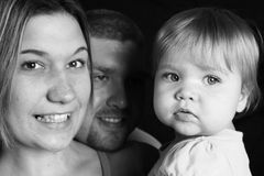 Happy Family, black and white. A mother and daughter smile for the camera as dad looks on, black and white Royalty Free Stock Images