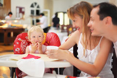 Happy family with blond little girl eating bread Stock Images
