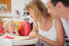 Happy family with blond little girl eating bread Royalty Free Stock Image