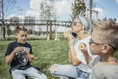 Happy family blowing bubbles outdoors in the park and having fun. royalty free stock photos