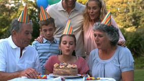 Happy family blowing the candles of birthday cake stock video