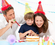 Happy family blowing candles together Stock Image