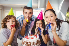 Happy family blowing party horn during birthday celebration Stock Photos