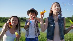 Happy family blowing soap bubbles on nature near river on background heaven in summer. Happy family blowing soap bubbles on nature near river on background blue stock footage