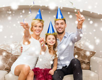 Happy family in blue hats throwing serpentine Stock Photos