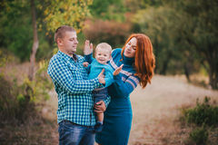 Happy family in blue stylish clothes walking in autumn forest Stock Photography
