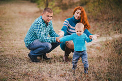 Happy family in blue stylish clothes walking in autumn forest Stock Photos