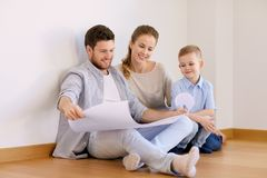 Happy family with blueprint moving to new home Stock Image