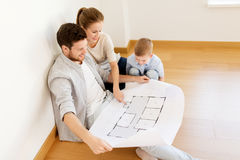 Happy family with blueprint moving to new home. Mortgage, people, housing and real estate concept - happy family with blueprint or house project moving to new Stock Images
