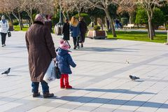 Happy family on boulevard. The grandmother with granddaughter feed pigeons Royalty Free Stock Images
