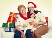 Happy family with box gift, woman with child and elderly - holiday concept Stock Image