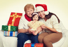 Happy family with box gift, woman with child and elderly - holiday concept Royalty Free Stock Photography
