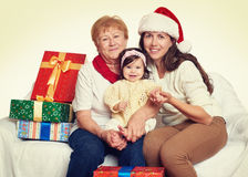 Happy family with box gift, woman with child and elderly - holiday concept Stock Photo