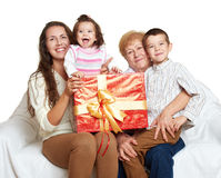 Happy family with box gift, woman with child and senior - holiday concept Royalty Free Stock Image