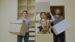 Happy family with boxes in a new house. Happy family relocates in a new house. Two little girls stands in front of camera in a new room and holds boxes with stock footage