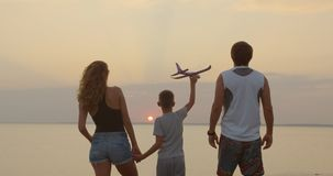 A happy family. The boy with his father and mother with toy airplane at the sunset. stock video footage
