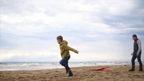 Happy family. Boy with his father playing on the beach. Boy launching kite stock footage