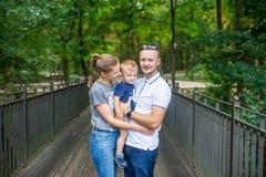 Happy family on bridge in summer city park royalty free stock photography