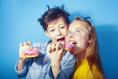 Happy family brother and sister eating donuts on blue background, lifestyle people concept, boy and girl eating. Unhealthy closeup stock images