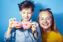 Happy family brother and sister eating donuts on blue background, lifestyle people concept, boy and girl eating. Unhealthy closeup royalty free stock images